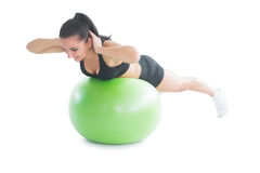 Cute fit woman practicing an exercise on a fitness ball Royalty Free Stock Image