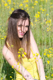 Cute fit young lady standing among yellow blooming field Stock Image