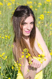 Cute fit young lady standing among yellow blooming field Stock Photography
