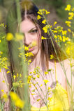 Cute fit young lady standing among yellow blooming field Stock Photos