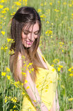 Cute fit young lady standing among yellow blooming field Royalty Free Stock Photos