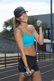 Cute and beautiful teen girl fitness model outside. Cute and fit young teen Caucasian girl working out on outdoor track laughs as she does bicep curls with Stock Photo