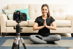 Cute fitness blogger doing some yoga. Gorgeous young Hispanic fitness blogger giving some advice on practicing yoga at home on video Stock Photography