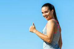 Cute fitness girl doing thumbs up outdoors. Royalty Free Stock Photos