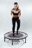 Cute fitness-girl make exercise on rebounder Stock Images