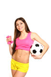 Cute fitness girl posing with dumbbells and a soccer ball on a w Stock Photos