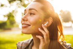 Cute fitness sports woman in park outdoors listening music with earphones. Stock Image