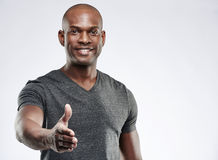 Cute fitness trainer reaching to shake hands. Single cute young Black male fitness trainer in gray compression shirt reaching out toward camera to shake hands Stock Image