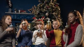 Cute five children cheers cup of tea on the Christmas tree background in cozy room. Cute happy five children in stylish sweater cheers with the cup and drinking stock footage