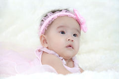 Cute five months asian baby in pink dress., on soft carpe Stock Photos