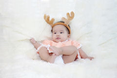 Cute five months asian baby in reindeer horns., on bright soft carpet Stock Photo