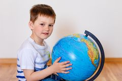Cute five year old boy has his hands on the globe and looks at the camera royalty free stock image