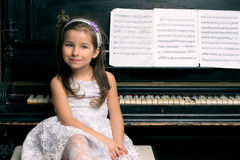 Cute 5 year old girl sitting by piano. Cute five year old girl sitting by the piano black Stock Photos
