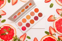 Cute flat lay with palette of cosmetics with fresh fruit, cut strawberries and grapefruit or red orange, mint leaves. On a white background royalty free stock photos