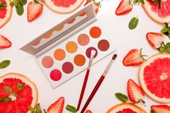 Cute flat lay with palette of cosmetics with fresh fruit, cut strawberries and grapefruit or red orange, mint leaves. On a white background royalty free stock photography
