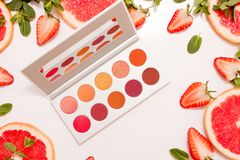 Cute flat lay with palette of cosmetics with fresh fruit, cut strawberries and grapefruit or red orange, mint leaves. On a white background stock photography