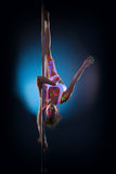 Cute flexible girl hanging upside down on pylon Royalty Free Stock Image
