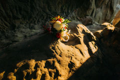 Cute floral bouquet on rock in yellow sunset lights.  royalty free stock images