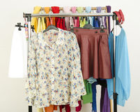 Cute floral outfits displayed on a rack. Wardrobe with colorful Stock Photography