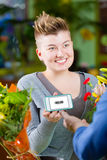 Cute Flower Shop  Customer using Electronic Coupon. Cute female customer in store showing clerk phone with electronic coupon displayed Stock Images
