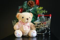 Cute fluffy teddy bear and coins in mini trolley with Mini Christmas tree decoration  on dark black background. Year end, Christmas and holiday conceptual Royalty Free Stock Photo