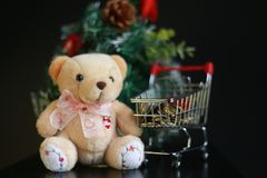 Cute fluffy teddy bear and coins in mini trolley with Mini Christmas tree decoration  on dark black background. Year end, Christmas and holiday conceptual Stock Photo