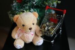 Cute fluffy teddy bear and coins in mini trolley with Mini Christmas tree decoration  on dark black background. Year end, Christmas and holiday conceptual Stock Images