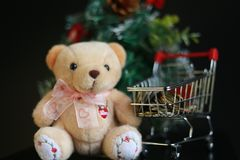 Cute fluffy teddy bear and coins in mini trolley with Mini Christmas tree decoration  on dark black background. Year end, Christmas and holiday conceptual Royalty Free Stock Image