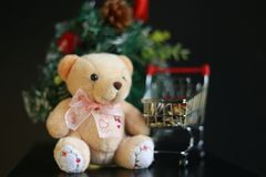 Cute fluffy teddy bear and coins in mini trolley with Mini Christmas tree decoration  on dark black background. Year end, Christmas and holiday conceptual Stock Photos
