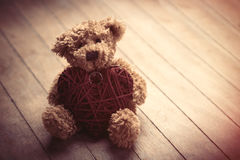 Cute fluffy teddy bear with heart shaped toy on the wonderful br Royalty Free Stock Photo