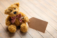 Cute fluffy teddy bear with label on the wonderful brown wooden Stock Images