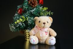 Cute fluffy teddy bear with Mini Christmas tree decoration  on dark black background. Year end, Christmas and holiday conceptual image Stock Photography