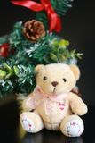 Cute fluffy teddy bear with Mini Christmas tree decoration  on dark black background. Year end, Christmas and holiday conceptual image Royalty Free Stock Photography