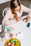 Cute focused child painting easter egg at table royalty free stock photography