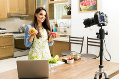 Cute food blogger recording a video. Good looking young female food blogger giving some cooking tips on video Stock Image