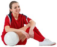 Cute football player sitting with ball Royalty Free Stock Photos