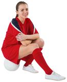 Cute football player sitting with ball Royalty Free Stock Image