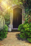 Cute footpath leads to arched entry surrounded by lush foliage Stock Images