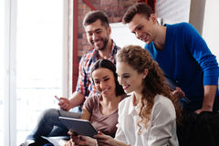 Cute four students are making fun with gadget Stock Image