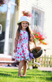 Cute four-year girl carrying a basket Royalty Free Stock Photos