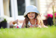 Cute four-year girl lying on the grass Royalty Free Stock Image