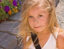 Cute Four Year Old Girl. This cute 4 year old bi-racial girl is outdoors with her blond hair wisping around her cute face Stock Photo