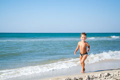 Cute four years boy is running in sea Stock Photo