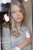 Cute freckles girl behind window stock photos