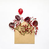 Cute fresh berries and leaves in an envelop on white background. Stylish flat lay. Minimal concept Stock Images