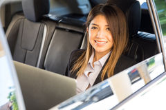 Cute and friendly businesswoman in a car Stock Images