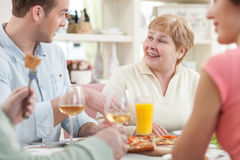 Cute friendly family is dining with joy Stock Photo
