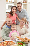 Cute friendly family is spending time together. There is no place like home. Portrait of mature married couple sitting at the table with their granddaughter. The royalty free stock image