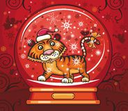 Cute friendly tiger inside of the snow-dome. Cute friendly tiger, wearing Santa cap, with candy cane tale. Inside of the snow-dome. 2010 is the Year of the Stock Images