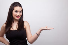 Cute friendly woman showing or holding stock images